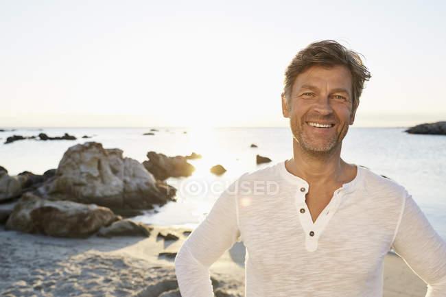 Зрелый мужчина стоит на пляже — стоковое фото