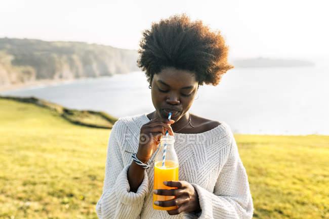 Женщина пьет апельсиновый сок — стоковое фото