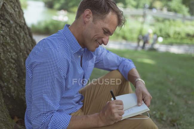 Человек с блокнотом сидит в парке — стоковое фото