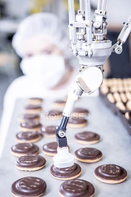 Roboterhandling Cookies mit Frau im Hintergrund — Stockfoto