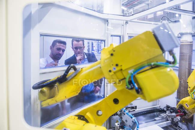 Hommes, examinant la machine robotique — Photo de stock