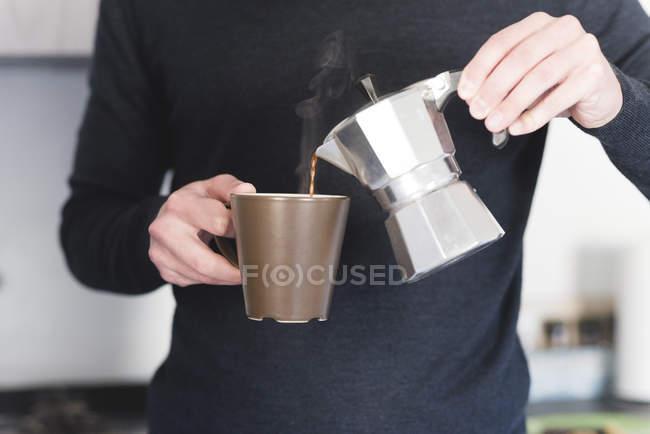 Человек наливает горячий эспрессо в кружку — стоковое фото
