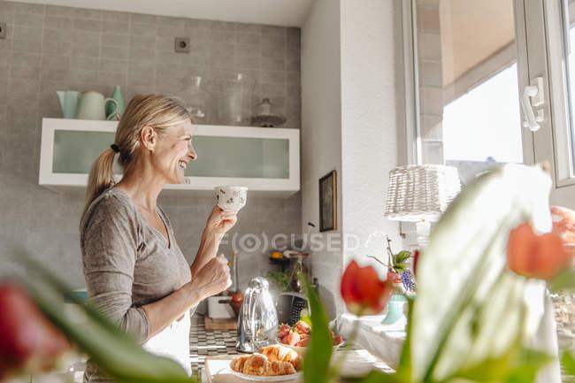 Жінка дивиться з вікна кухні — стокове фото