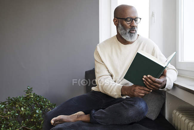 Mature man reading book near window — Stock Photo