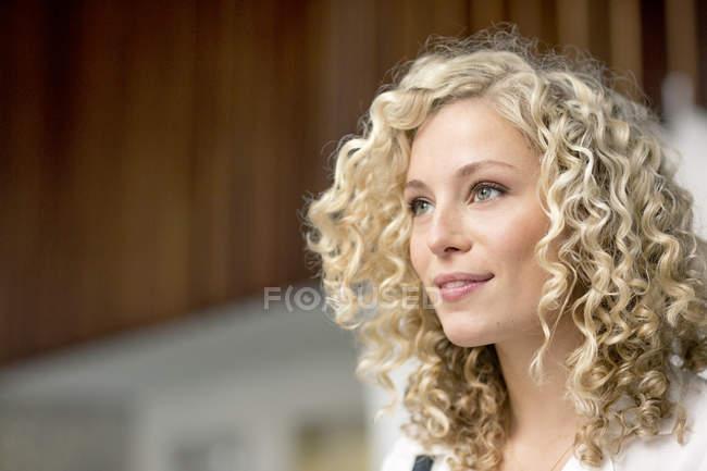 Портрет улыбающейся блондинки-предпринимательницы с колечками — стоковое фото