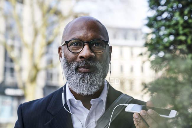 Бізнесмен в окуляри, навушники і смартфонів — стокове фото