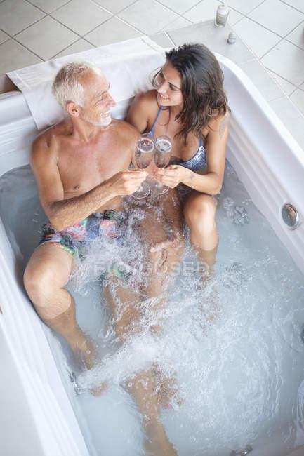 Зріла людина з молодшим жінка насолоджуючись шампанським напої в гарячій ванні джакузі — стокове фото
