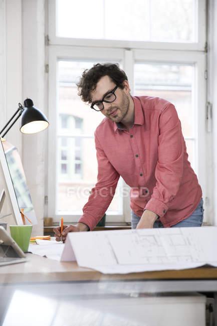 Man working on blueprint at desk — Stock Photo