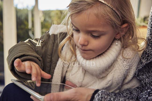 Chica con madre usando tableta - foto de stock