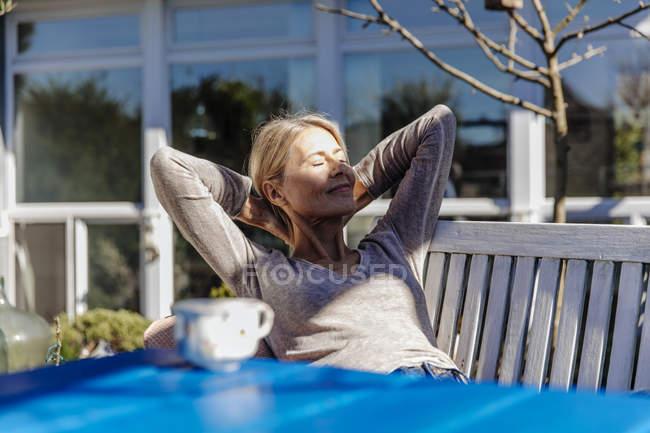 Donna rilassante su panca da giardino — Foto stock