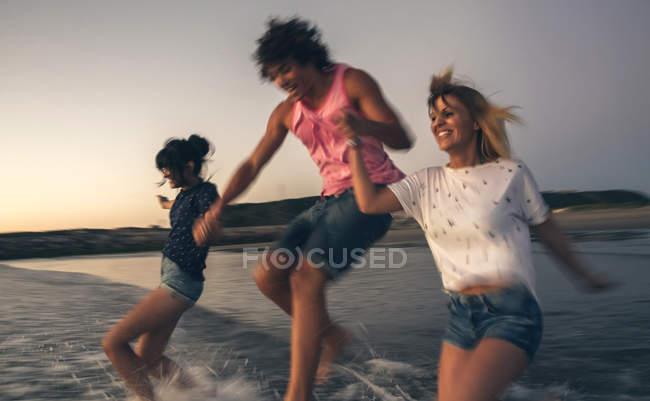 Amigos felizes de mãos dadas e correndo para o mar ao entardecer — Fotografia de Stock