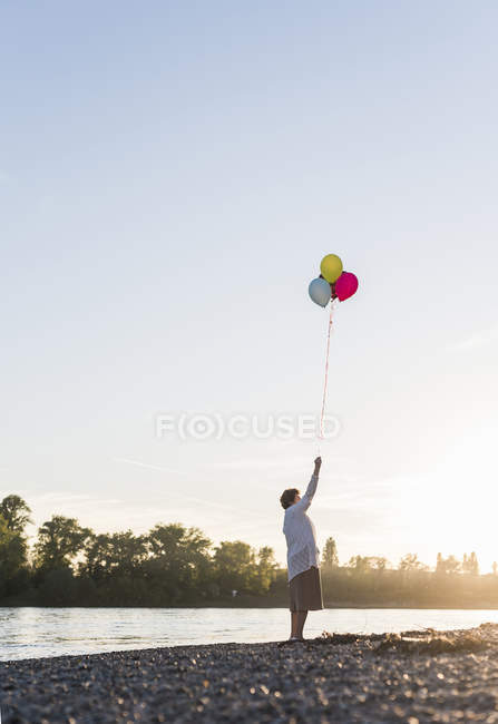 Woman with balloons on beach — Stock Photo