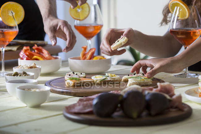 Hands reaching for appetizers — Stock Photo