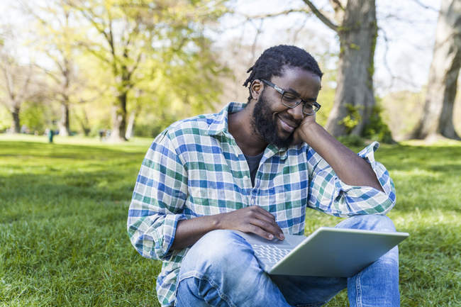 Man sitting on meadow and using laptop — Stock Photo