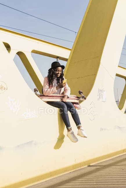 Woman sitting on bridge using and smartphone — Stock Photo