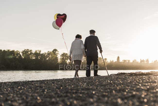 Couple with balloons strolling at riverside — Stock Photo