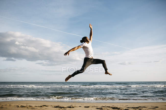 Man jumping in air on beach — Stock Photo