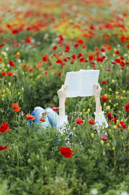Woman lying in field and reading — Stock Photo