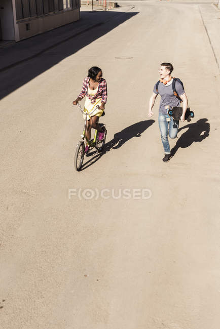 Couple running and biking in street — Stock Photo