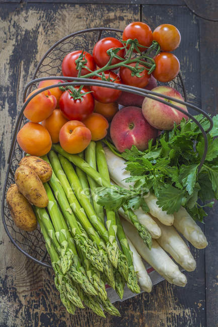 Wire basket of various fruits and vegetables — Stock Photo