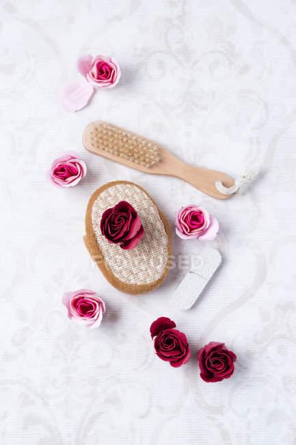Ванные розы, массажная губка, пемза и кисть на ткани — стоковое фото