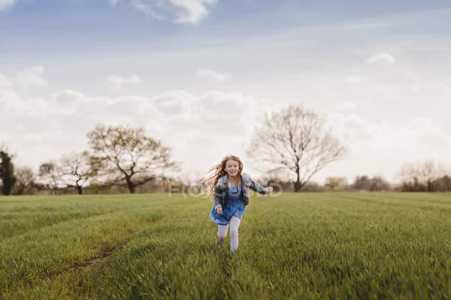e571a07b763010 Mädchen läuft auf grüner Wiese — Stockfoto