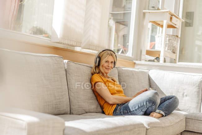 Женщина, сидящая на диване в наушниках — стоковое фото