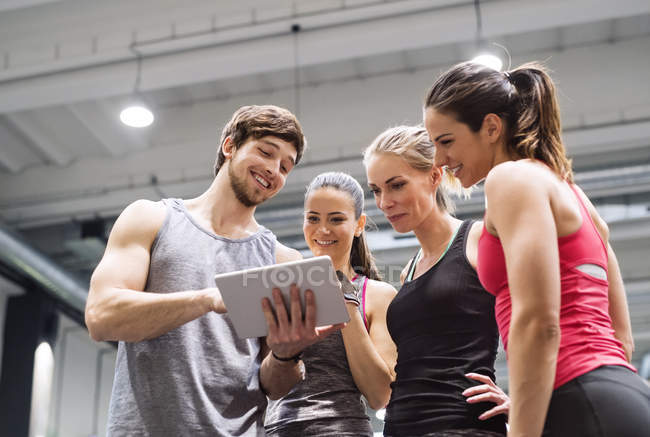 Happy athletes with tablet in gym — Stock Photo