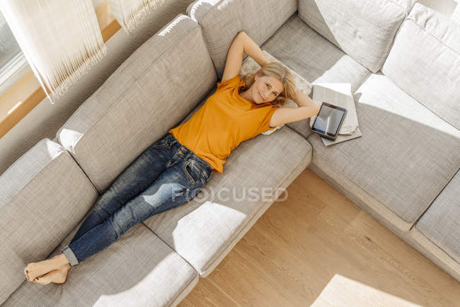 Woman lying on couch — Stock Photo