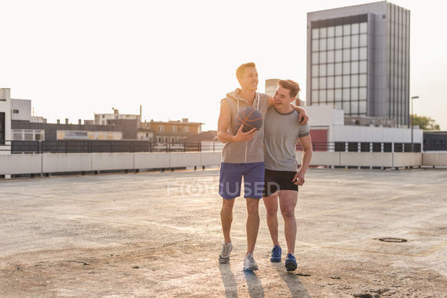 Friends playing basketball on rooftop — Stock Photo