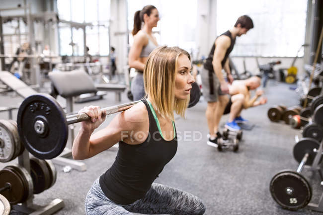 Woman lifting weights in gym — Stock Photo