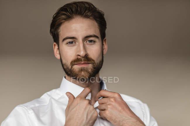 Businessman buttoning collar of shirt — Stock Photo