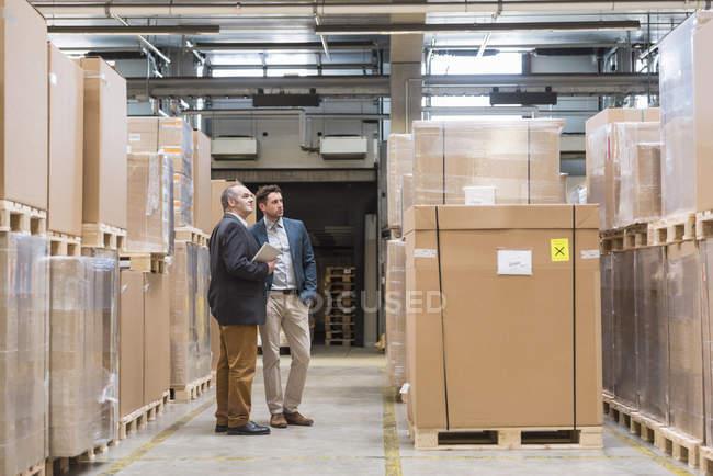 Deux hommes debout dans l'entrepôt de l'usine — Photo de stock