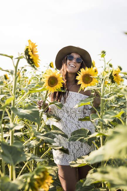 Женщина, стоящая на подсолнечном поле — стоковое фото