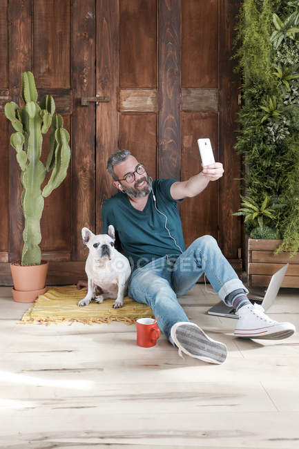 Бородатий людина з собакою, беручи selfie — стокове фото