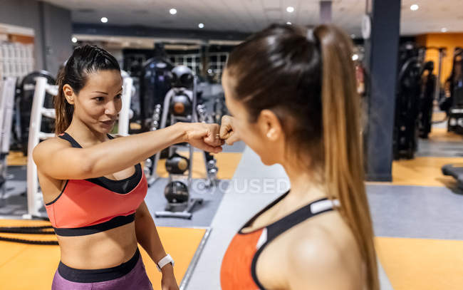 Women doing fist bump in gym — Stock Photo