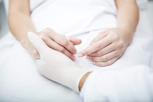 Doctor holding patient hand — Stock Photo