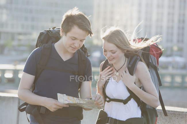 Alemanha, Berlim, Casal jovem viajando Berlim com mochilas, olhando para o mapa — Fotografia de Stock