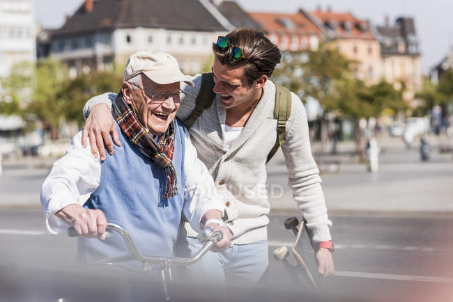 Senior man with adult grandson in city — Stock Photo