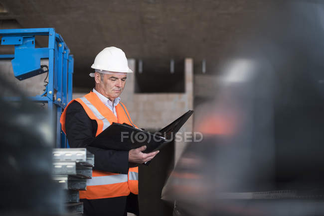 Man standing with documents in building under construction — Stock Photo