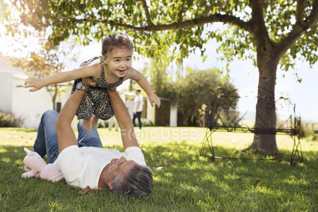 Padre jugando con su hija en el jardín - foto de stock