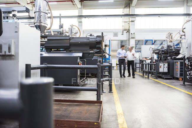 Hombres con tableta caminando en fábrica - foto de stock