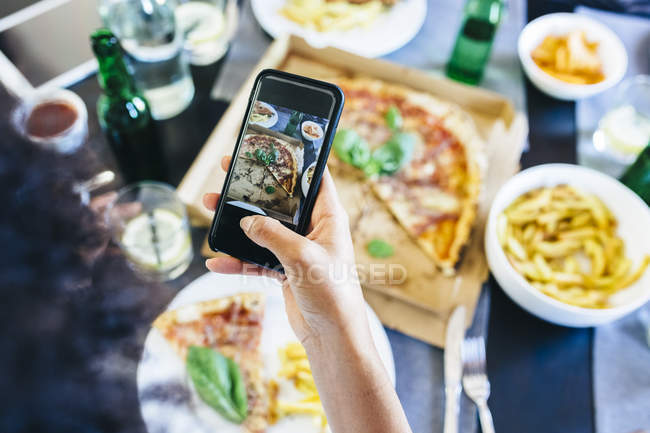 Hand taking cell picture of pizza — Stock Photo