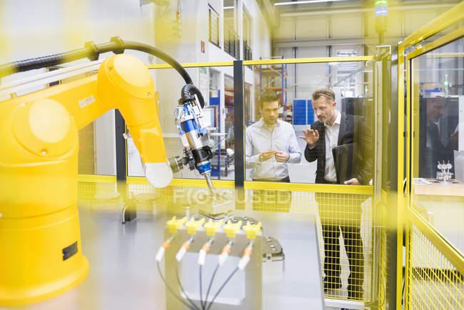 Businessmen observing industrial robot — Stock Photo