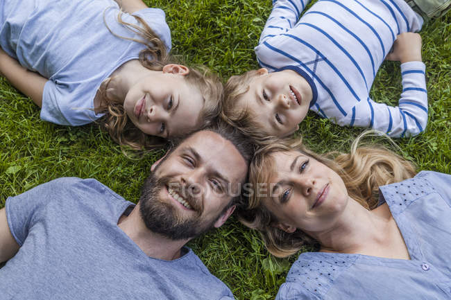 Family lying in meadow — Stock Photo