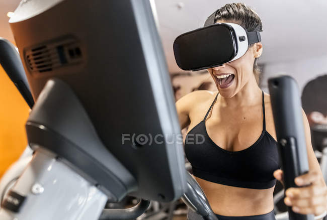 Woman wearing VR glasses on elliptical trainer — Stock Photo