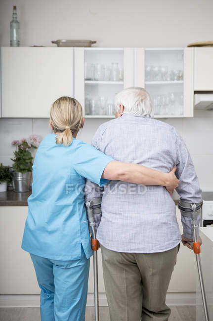 Gereatric nurse supporting patient — Stock Photo