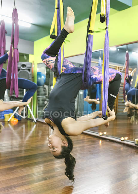 Women practicing aerial yoga in class — Stock Photo