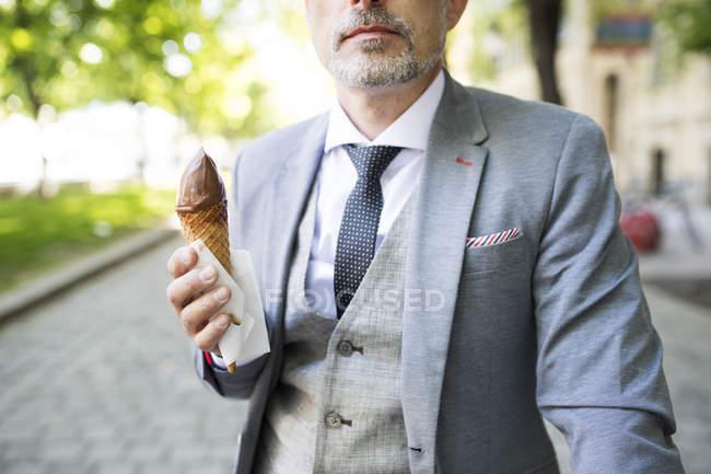 Бизнесмен ест мороженое — стоковое фото