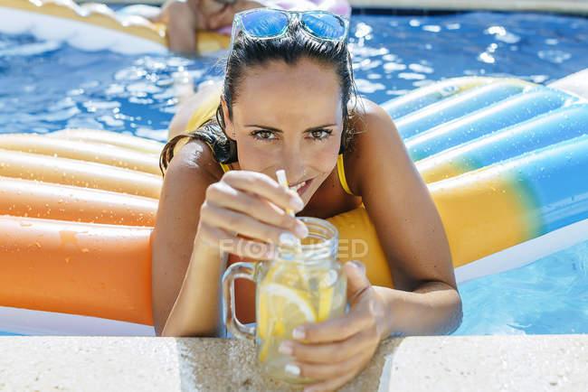 Mulher na piscina com bebida — Fotografia de Stock